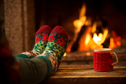 Feet in woollen socks by the Christmas fireplace. Woman relaxes by warm fire with a cup of hot drink and warming up her feet in woollen socks. Close up on feet. Winter and Christmas holidays concept.