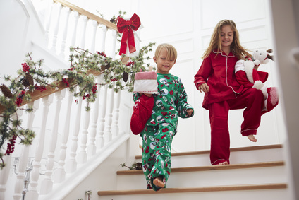 Two Children On Stairs In Pajamas With Christmas Stockings
