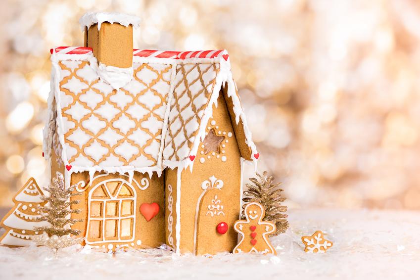 Homemade gingerbread house scene on warm bokeh background