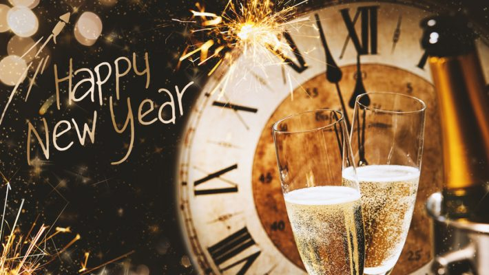 Happy New Year greeting card with champagne in front of a clock counting down to midnight and a sparkling bokeh of party lights and sparklers