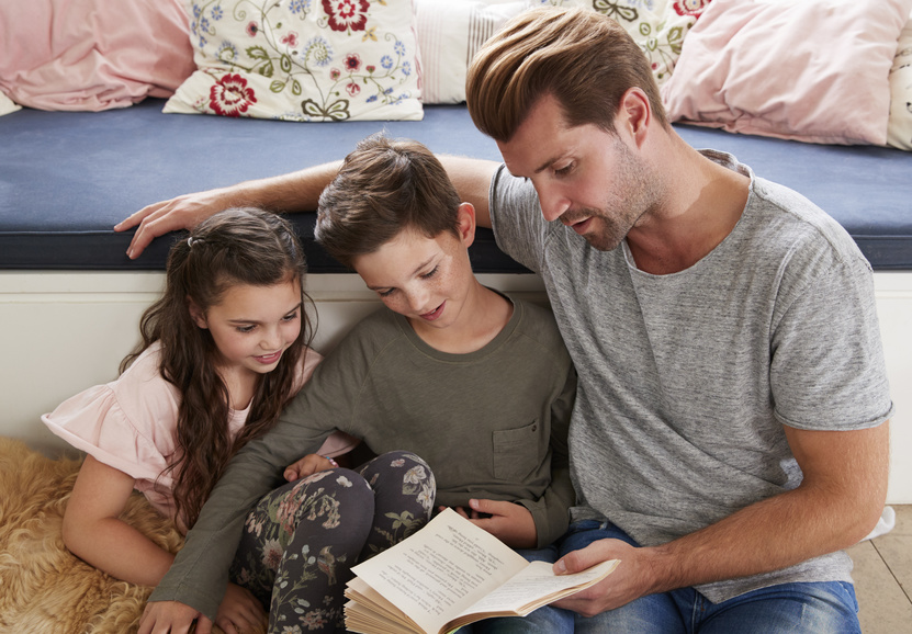 Father Reading Book With Son And Daughter At Home