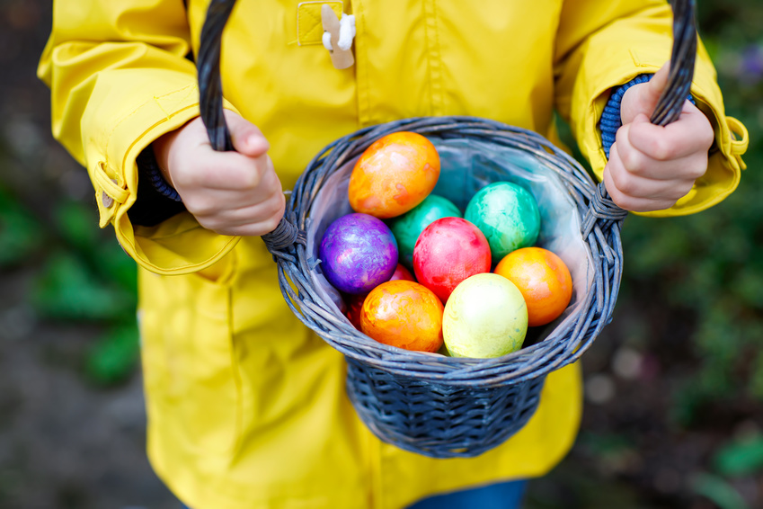 Close-up of hands of little child with colorful Easter eggs in basket. Kid making an egg hunt. child searching and finding colorful eggs in domestic garden. Old christian and catholoc tradition