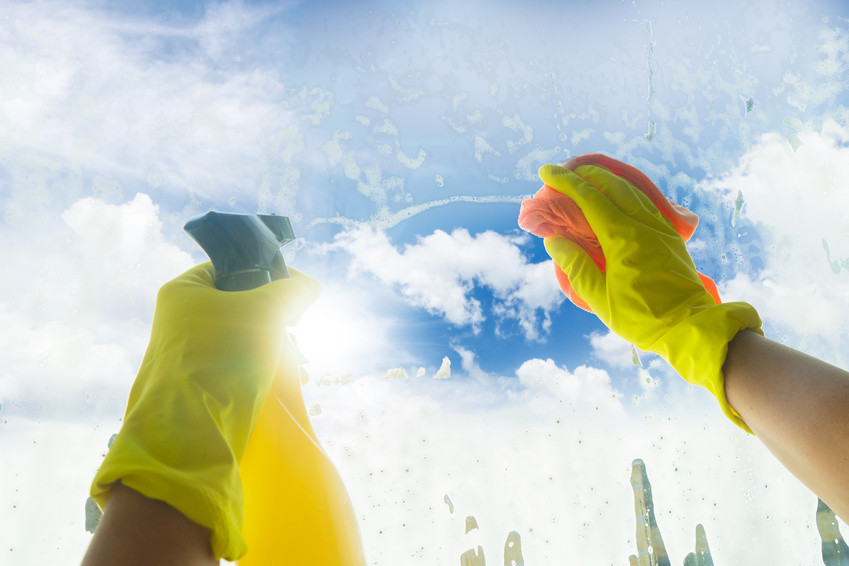 Spring cleaning - someones hands in yellow gloves with spray and ruber cleaning window, spring blue sky in background